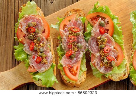 Sandwiches With Ham, Salad Leaves, Chili, Tomatoes, Capers, French Mustard On Wooden Background