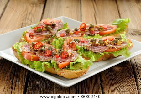 Sandwiches With Ham, Salad Leaves, Chili, Tomatoes, Capers, French Mustard In White Plate On Wooden