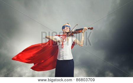 Young confident woman in red cape and mask playing violin