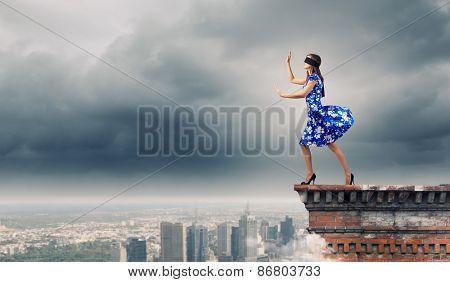 Young woman in blue dress standing on roof edge