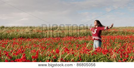 Happy Teenage Girl Standing  In A Red Field Of Poppy Flowers