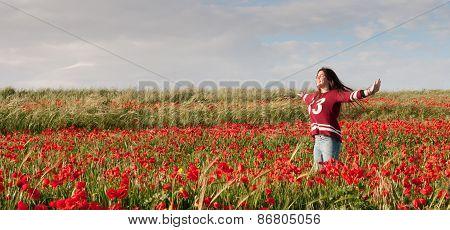 Happy Teenage Girl Standing  In A Red Field Of Poppy Flowers