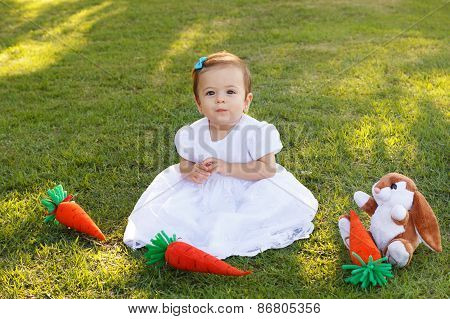 Cute Little Baby Girl In White Dress With Toy Rabbit And Carrot On Green Grass In Park