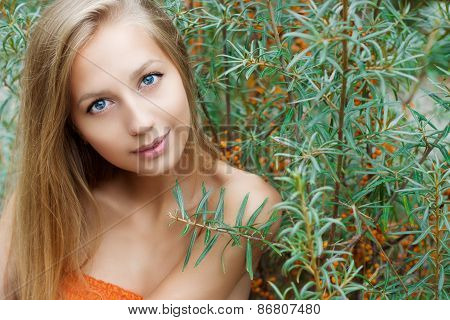 beautiful sexy girl with big lips long hair with dark skin sits near sea buckthorn summer on a warm