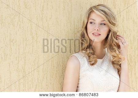 Portrait of a beautiful sexy smiling happy girl with big full lips with blond hair in a white dress