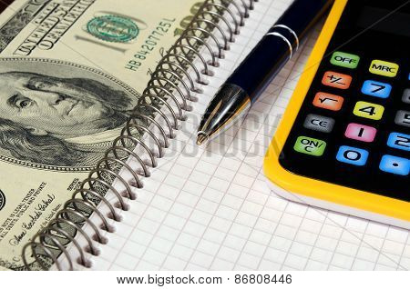 Dollars and calculator. Business still-life with objects of business