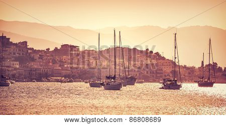 Sail boats in mild orange sunset light, coastal yacht port in islands of Greece, touristic place, summer travel and vacation