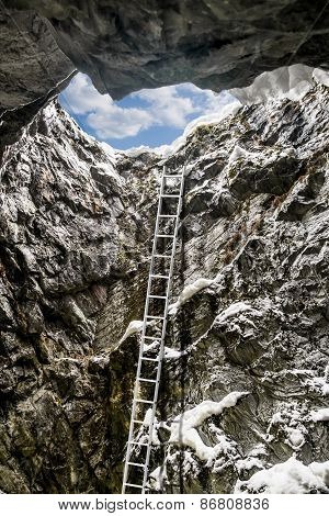 Ladder In A Vertical Tunnel In The Mountains And The Sky In A Skylight On Top