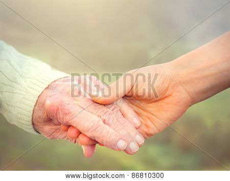 Elderly Woman Holding Hands With Young Caregiver