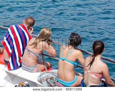 Passengers in swimming gear sitting on the boat