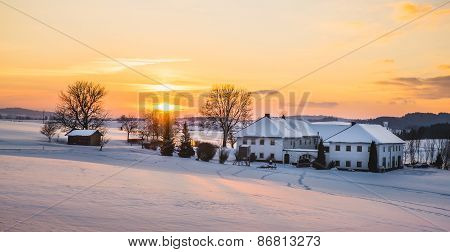 Farmhouse in a winter landscape at sunrise