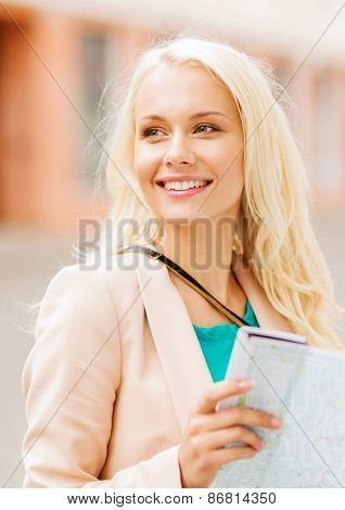 holidays and tourism concept - beautiful girl looking into tourist map in the city