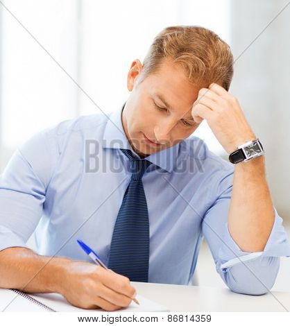 picture of handsome businessman writing in notebook