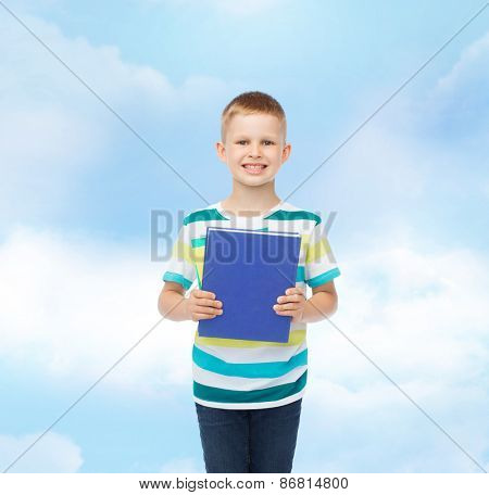 education, childhood and school concept - smiling little student boy with blue book over blue cloudy sky background