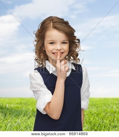 people, children, secrecy and mystery concept - happy girl showing hush gesture over blue sky and grass background