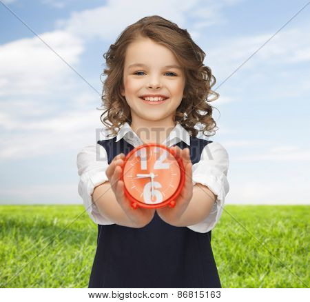 people, childhood, time and punctuality concept - happy girl with alarm clock over blue sky and grass background