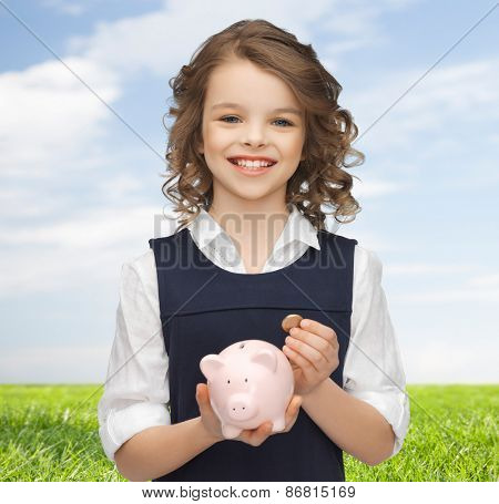people, money, finances and savings concept - happy girl holding piggy bank and coin over blue sky and grass background