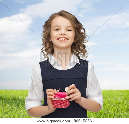 finances, childhood, people, money and savings concept - happy little girl with purse and euro coin over blue sky and grass background