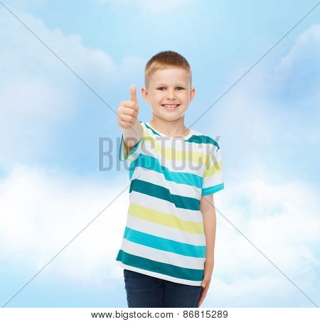 happiness, childhood and people concept - smiling little boy in casual clothes showing thumbs up over cloudy sky background