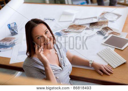 Woman talking over phone in office