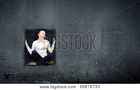 Young woman trapped in stone cube in wall