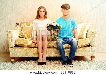 Young man and young woman sitting on opposite ends of the sofa. Relationship concept.