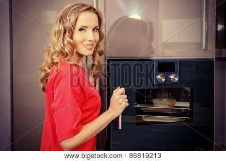 Elegant young woman cooking in the kitchen at home. Healthy eating. Home interior. Furniture.