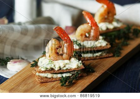 Appetizer canape with shrimp and cucumber on cutting board on table close up