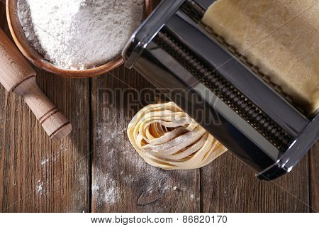 Making noodles with pasta machine on wooden table, top view