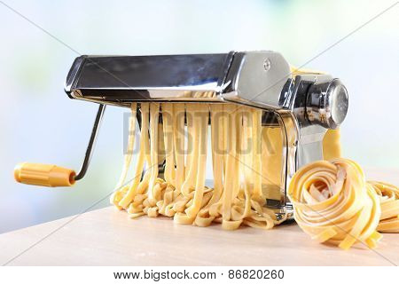 Making noodles with pasta machine on light background