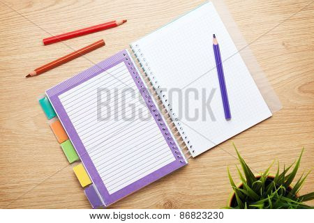 Office table with flower, blank notepad and colorful pencils. View from above with copy space