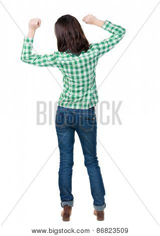 Back view joyful woman celebrating victory hands up. Rear view people collection. backside view person. Isolated over white background. slender brunette in a jeans shows symbol success or hitchhiking