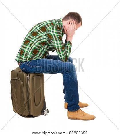 back view man sitting on suitcase. waiting at station. backside view person.  Rear view people collection. Isolated over white background. guy with a travel bag on wheels looking at something at top