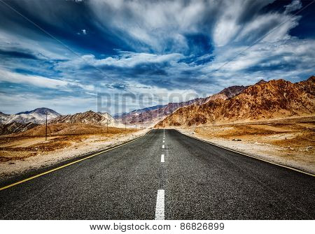 Travel forward concept background - road in Himalayas mountains and dramatic clouds. Ladakh, Jammu and Kashmir, India