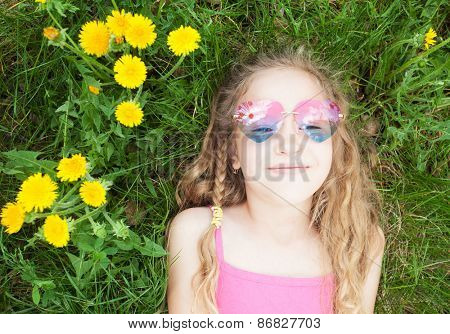 Child at summer. Happy girl outdoors on green grass