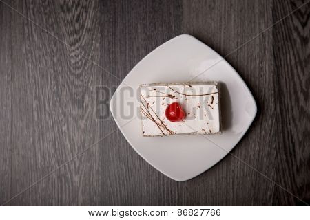 Creamy cake with cherry on white plate, top view