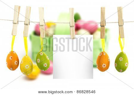 hanging easter eggs against colourful little easter eggs in a green wicker basket