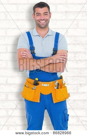 Repairman in overalls wearing tool belt standing arms crossed against white wall