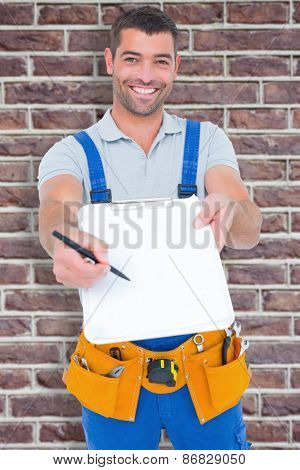 Smiling handyman giving clipboard for signature against red brick wall
