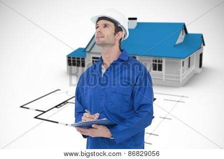 Supervisor writing notes on clip board against blue house behind an architectural plan