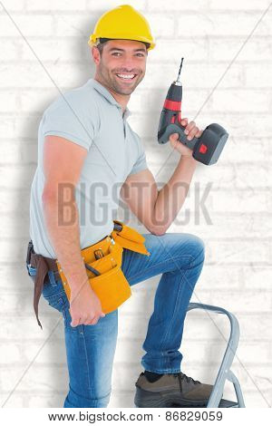Confident handyman holding power drill while climbing ladder against white wall