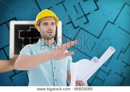 Architect with blueprint gesturing on white background against tablet displaying blueprint