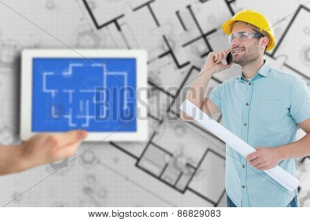 Male architect with blueprint talking on mobile phone against digital tablet displaying blueprint