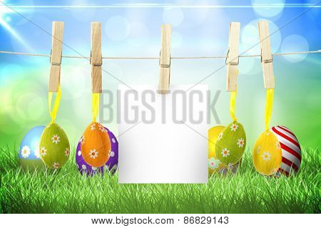 hanging easter eggs against colourful easter eggs on the grass