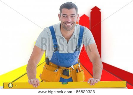 Worker using spirit level against orange red and yellow arrows