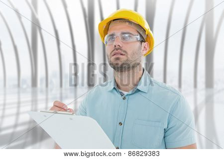 Supervisor looking away while writing on clipboard against white room with large window overlooking city