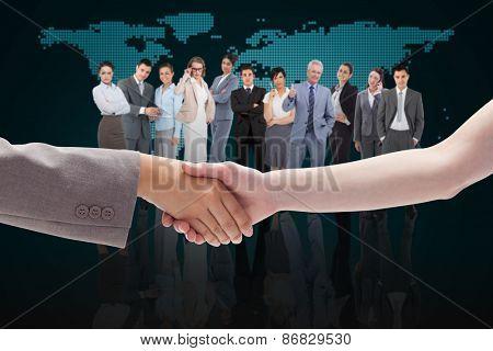 Handshake between two women against blue world map