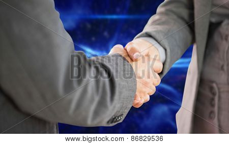 Business people shaking hands close up against blue abstract design
