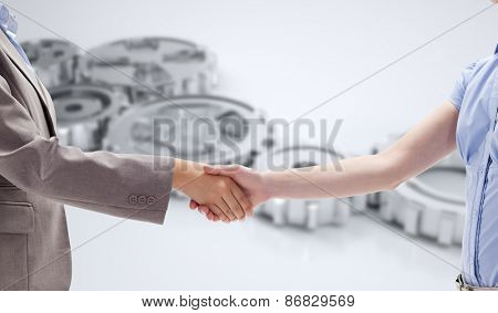 Handshake between two women against cogs and wheels