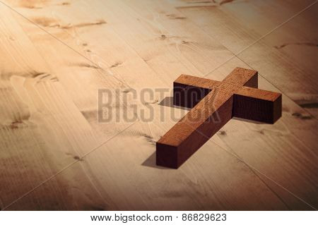 Wooden cross against bleached wooden planks background